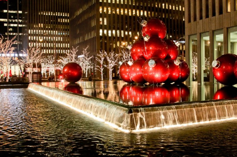 giant red ornaments piled on top of a fountain