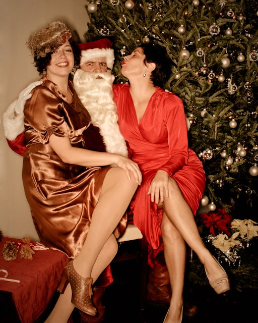 two ladies sitting on a happy santa